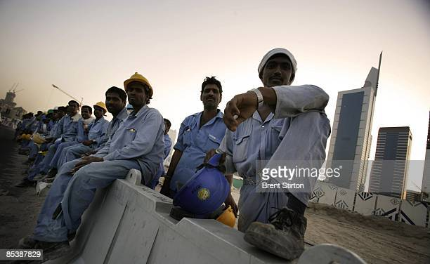Migrant construction labourers working in Dubai line up to board a bus which will take them back to their labour camp for the night on May 1, 2006 in...