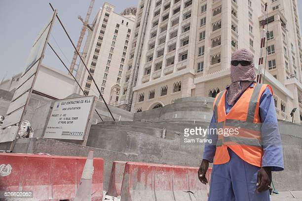 A migrant construction worker poses for a picture outside of their work site at The Pearl a manmade chain of islands off the coast of northern Doha...