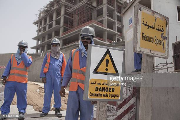 Migrant construction workers pose for a picture outside of their work site at The Pearl a manmade chain of islands off the coast of northern Doha...