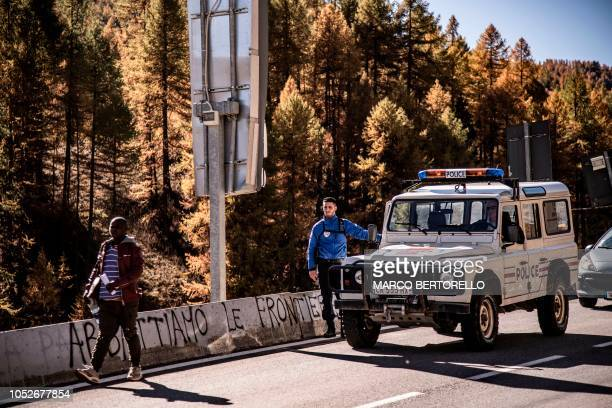 A migrant crosses on foot the border from France into Italy after being driven and pushed back by French Police on October 21 2018 in the Alpine...