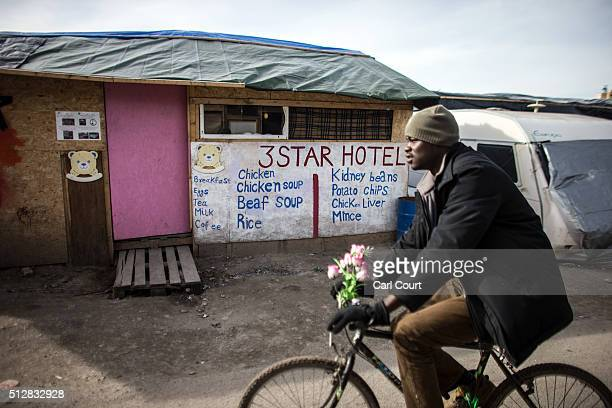 A migrant cycles past a cafe in the 'jungle' camp on February 28 2016 in Calais France The French authorities have begun dismantling part of the...