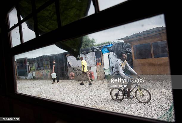 A migrant cycles past makeshift shops and shelters near to the Jungle Books Cafe at the Jungle migrant camp on September 6 2016 in Calais France The...