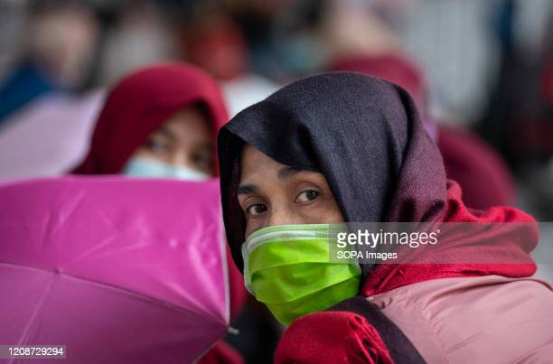 A migrant domestic worker looks on while wearing a protective mask during the lockdown amid Coronavirus pandemic Bars Mah Jong clubs gaming centers...