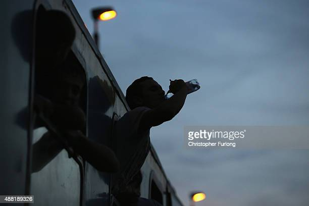 A migrant drinks from a bottle handed out by a volunteer aid worker to hundreds of migrants packed on a train at Roszke train station destined for...