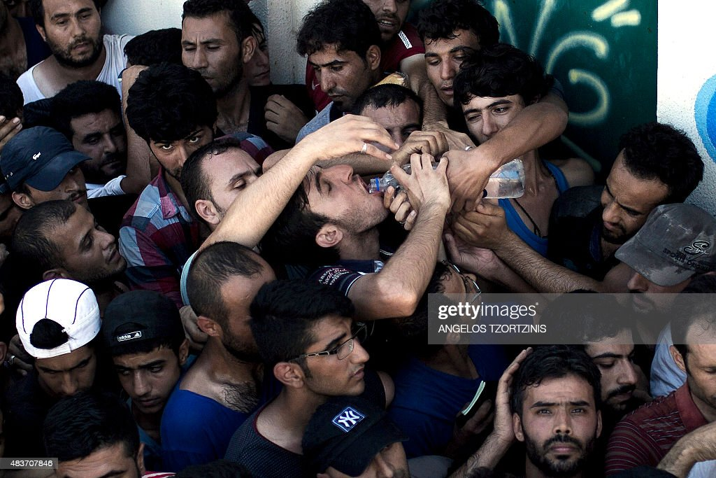 A migrant drinks water as he waits with hundreds of others to complete a registration procedure by the police at a stadium on the Greek island of Kos on August 12, 2015. Tensions on the tourist island are high with its mayor claiming there were 7,000 migrants stranded on Kos, which has a population of only 30,000 people. A Kos police officer was suspended on August 10 after being filmed slapping and shoving migrants queueing outside the local police station as they waited to be documented so they could go on to Athens. The UN refugee agency's division for Europe said 124,000 refugees and migrants have landed in Greece since the beginning of the year. / AFP / ANGELOS