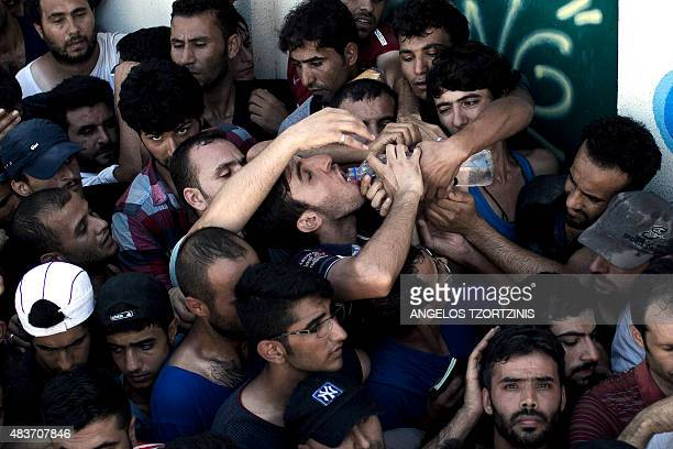 A migrant drinks water as he waits with hundreds of others to complete a registration procedure by the police at a stadium on the Greek island of Kos...