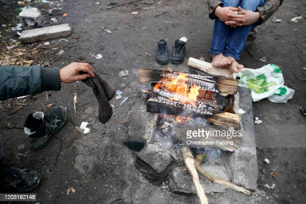 Migrant drys his socks next to a camp fire in a wood near the Calais Ferry terminal on January 31, 2020 in Calais, France. At 11.00pm on Friday 31st...