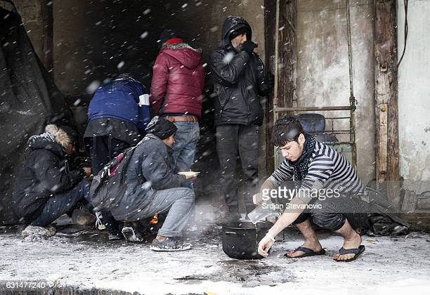 A migrant eats and wash a hands as snow falls outside a derelict customs warehouse on January 11 2017 in Belgrade Serbia It is estimated that around...