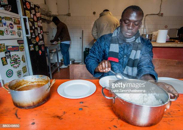 A migrant eats his meal in the kitchen in the 'CAS' center at the Caracol cooperative on November 27 2017 in Venice Italy The Caracol center hosts...