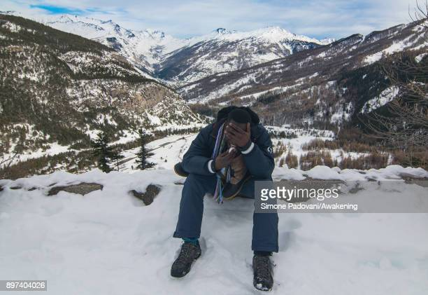 A migrant eats some snow climbing during another attempt to reach the French border through Colle della Scala on December 22 2017 in Bardonecchia...