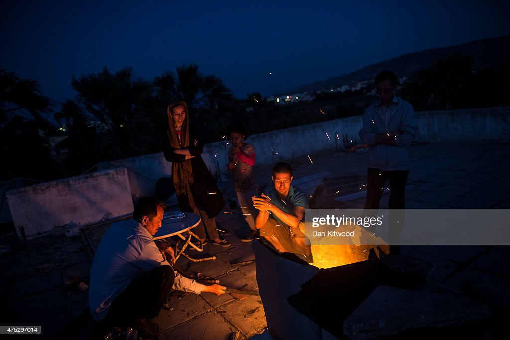 Migrant families heat food and keep warm on an open fire on the roof of an abandoned hotel that many migrants are using as temporary accomodation on May 30, 2015 in Kos, Greece. Many migrants are continuing to arrive on the Greek Island of Kos from Turkey. Around 30,000 migrants have entered Greece so far in 2015, with the country calling for more help from its European Union counterparts.