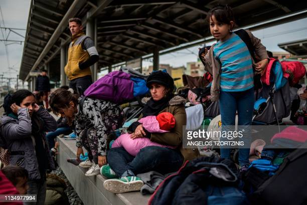 Migrant families sit on the train station platform and stand on the rails to block the way at Larissis railway central station in Athens on April 5...