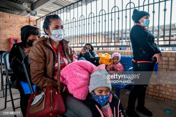 Migrant families wait for their bus at a bus station in Brownsville, Texas before travelling to meet relatives or sponsors on March 2, 2021. -...