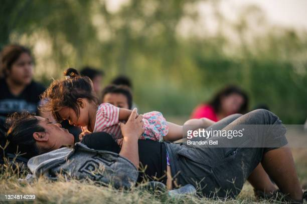 Migrant families wait to be accounted for and taken to a border patrol processing facility after crossing the Rio Grande into the U.S. On June 21,...