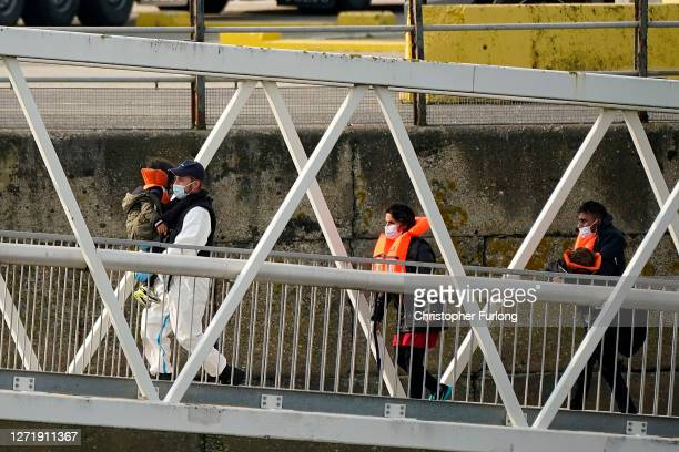 A migrant family disembark at Dover Marina after being rescued in the English Channel by the Border Force and RNLI on September 11 2020 in Dover...