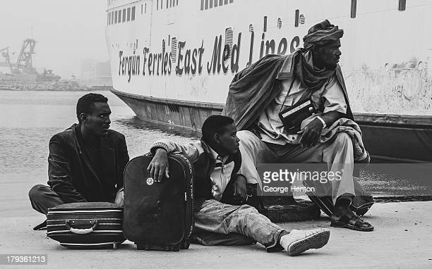 Migrant family from West Africa waits at the port in Benghazi, Libya, for a bus to take them across the border into Egypt, having just disembarked...
