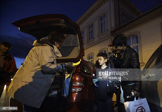 A migrant family is helped by a driver of an Austrian car rescue convoy to help and to transport migrant people in Budapest on September 6 2015 as...