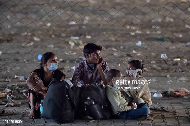 A migrant family sitting on the pavement after being stopped by Police at the Ghazipur Delhi Uttar Pradesh border on May 22 2020 in New Delhi India