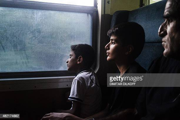A migrant family travels on a train heading north from Gevgelija to Tabanovce at the border with Serbia on July 27 2015 The absurd situation forced...
