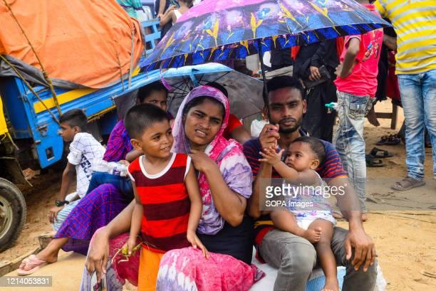 Migrant family waiting to travel home for Eid ul Fitr celebrations amid Coronavirus crisis. Migrants flock at the Shimulia-Kathalbari ferry terminal...
