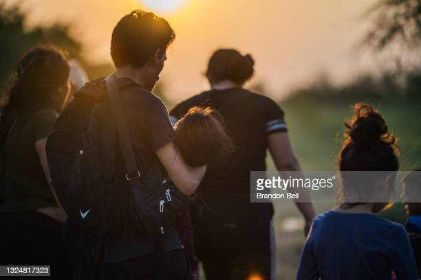Migrant family waits to be accounted for and taken to a border patrol processing facility after crossing the Rio Grande into the U.S. On June 21,...