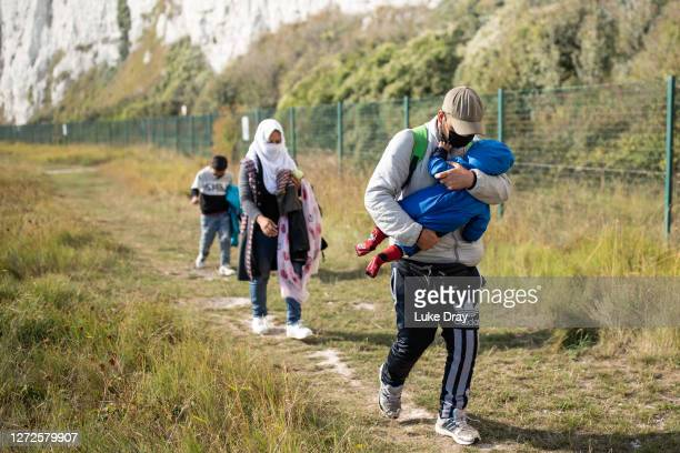 Migrant family walks along the coast on September 15, 2020 at Kingsdown Beach in Deal, England. More than 6,100 migrants have made the crossing by...