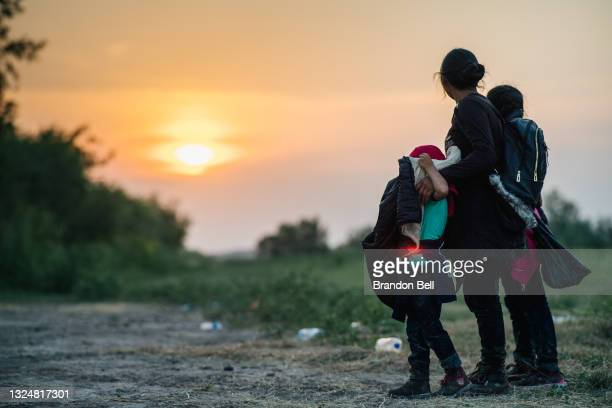 Migrant family watches the sunset while waiting to be accounted for and taken to a border patrol processing facility after crossing the Rio Grande...