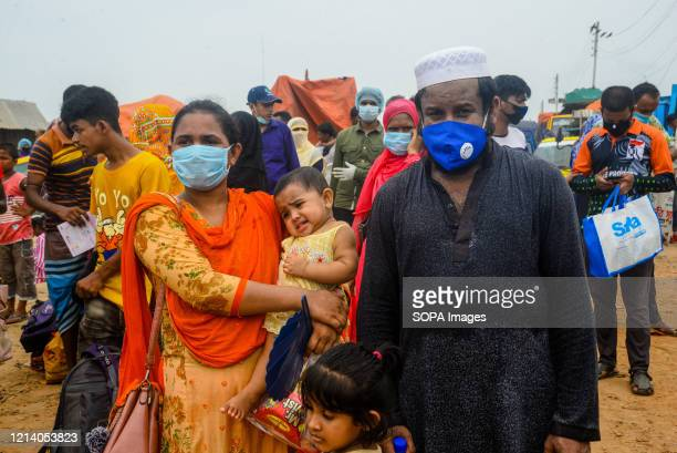 Migrant family wearing face masks wait for the ferry to travel home and for Eid ul Fitr celebration amid Coronavirus crisis. Migrants flock at the...