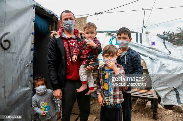A migrant family wearing handmade protective face masks stand next to their tent in the camp of Moria in the island of Lesbos on March 28 2020 as as...