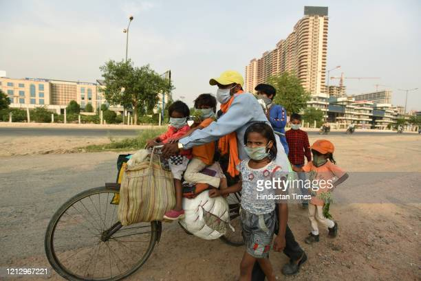 Migrant family with children were seen headed back to their village in Madhya Pradesh, near Gaur Chowk during lockdown, on May 13, 2020 in Noida,...