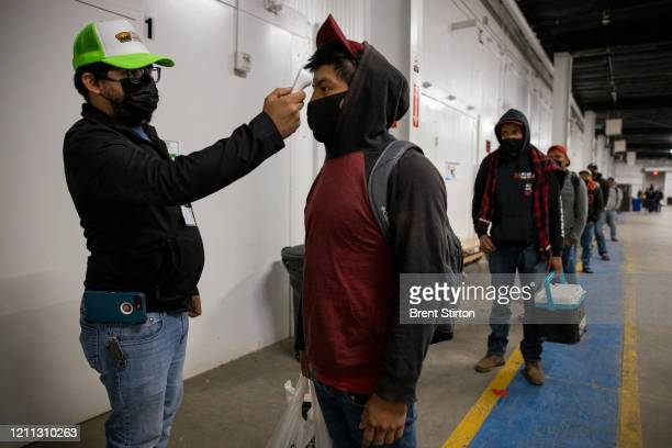 Migrant farm laborers with Fresh Harvest working with an H2A visa have their temperature checked and are asked questions about their health before...