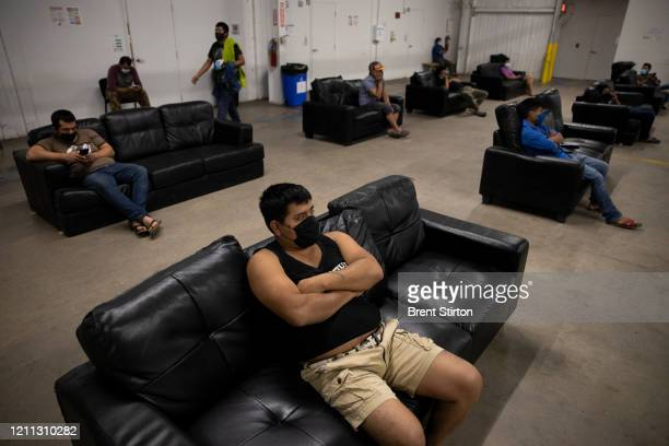 Migrant farm laborers with Fresh Harvest working with an H2A visa practice social distancing while watching TV in the company living quarters on...