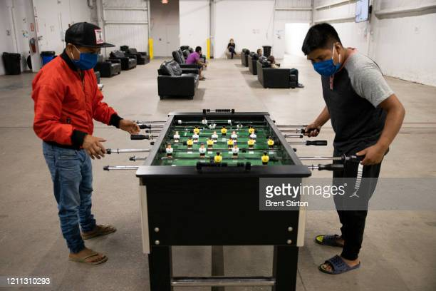 Migrant farm laborers with Fresh Harvest working with an H2A visa play foosball in the company living quarters on April 28 2020 in King City...