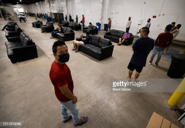 Migrant farm laborers with Fresh Harvest working with an H2A visa line up for a meal in the company living quarters on April 28 2020 in King City...