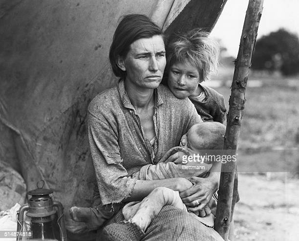A migrant farm worker mother sits with her two children Nipomo California March 1936