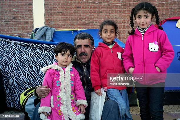 A migrant father and his three daughters pose for a photo in front of improvised shelter outside a passenger terminal at the port of Piraeus on March...
