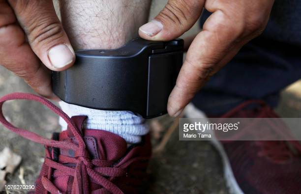 A migrant father from Guatemala who chose not to be identified demonstrates the ankle monitor he is required by ICE to wear 24 hours a day on...