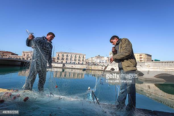 CONTENT] Migrant fishermen mending their nets at the Darsena in the island of Ortigia historical centre of Siracusa Sicily Italy