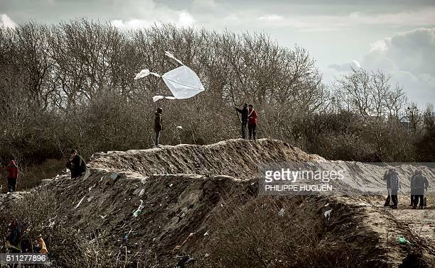 TOPSHOT A migrant flies a kite on February 19 2016 in the 'jungle' migrants and refugee camp in Calais northern France HUGUEN