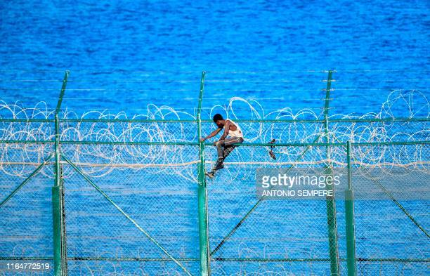 Migrant forces his way into the Spanish territory of Ceuta on August 30, 2019 . Over 150 migrants made their way into Ceuta after storming a...