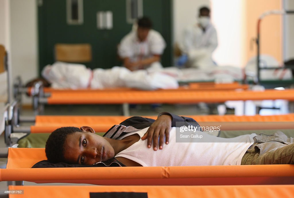 A migrant from Eritrea rests on a cot while waiting during his registration process at a center for migrants at a facility of the German Federal Police (Bundespolizei) on August 31, 2015 in Rosenheim, Germany. German police monitor trains arriving from the Balkans and from Italy that go through Rosenheim and currently detain around 350 people a day for travelling without a passport. The police register the migrants, mostly from countries including Syria, Afghanistan and Eritrea, fingerprint them and check whether any are already in the European asylum-applicants or criminal databases. From there the migrants are free to travel within Germany to reception centers where they can apply for asylum. Up to 1,600 migrants are currently arriving in Bavaria in southern Germany a day and will seek asylum. Germany is expecting to receive 800,000 asylum-seeking migrants this year and is struggling to cope with the record number.