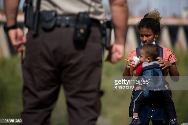 Migrant from Guatemala gives a baby water to drink as they wait to be processed after turning themselves over to authorities at the US-Mexico border...