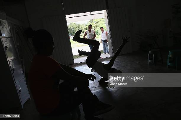 A migrant from Guatemala shows off his dance skills while stopping pass the Doctors Without Borders clinic on August 6 2013 in Ixtepec Mexico The...