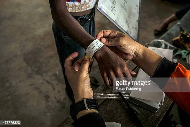 A migrant from Myanmar gets a band during an identification process by Indonesian authorities and the International Organization at a temporary...