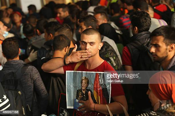 A migrant from Syria holds a picture of German Chancellor Angela Merkel as he and approximately 800 others arrive from Hungary at Munich Hauptbahnhof...