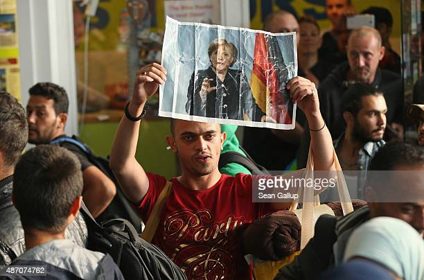 Migrant from Syria holds a picture of German Chancellor Angela Merkel as he and approximately 800 others arrive on a train from Hungary at Munich...