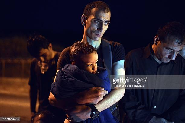 Migrant from Syria holds his baby as they arrived on the island of Lesbos, early on June 18, 2015. Some 48,000 migrants and refugees have landed on...