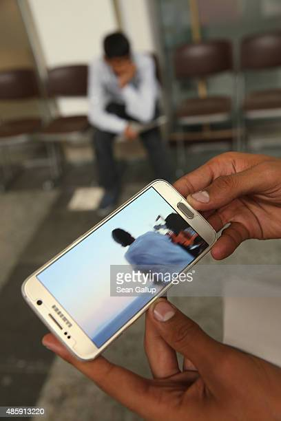 A migrant from Syria in a police holding area at Munich Hauptbahnhof main railway station shows the photographer a video on his smartphone that...