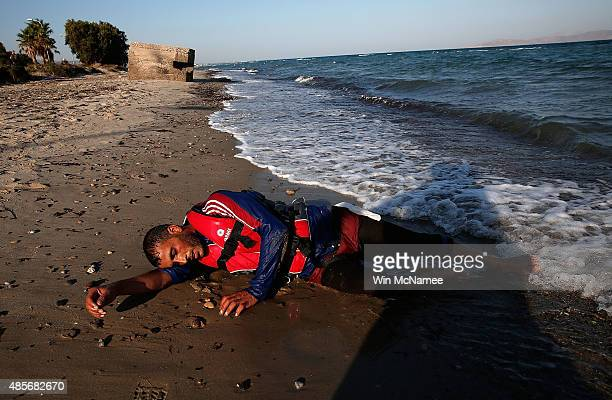 A migrant from Syria lays exhausted on the beach after paddling a small boat across a three mile stretch of the Aegean Sea from Turkey on August 29...