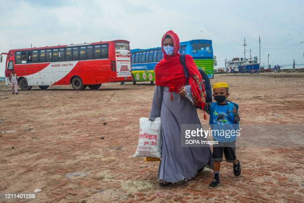 Migrant garment worker and her son are seen at Mawa ferry ghat. The government of Bangladesh has eased the restrictions over transportation and...